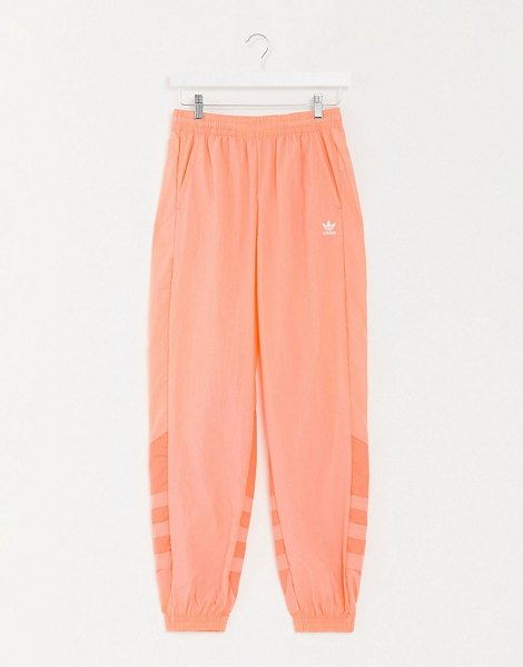 adidas Originals large trefoil track pants in coral-orange in orange