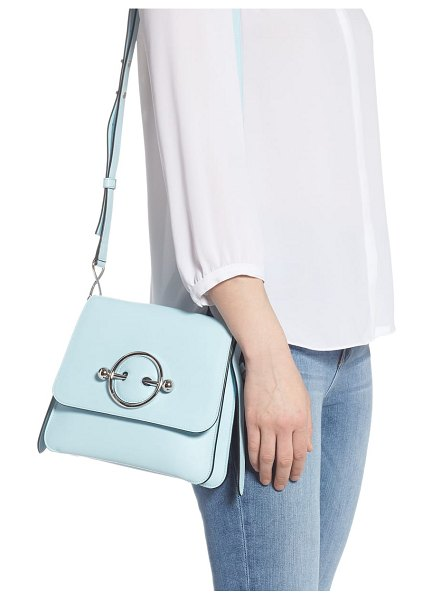 J.W.ANDERSON disc crossbody bag in blue - Signature ring hardware pierces the flap of a punk-chic...