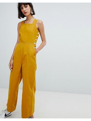 ASOS DESIGN denim jumpsuit with side buttons in mustard-yellow